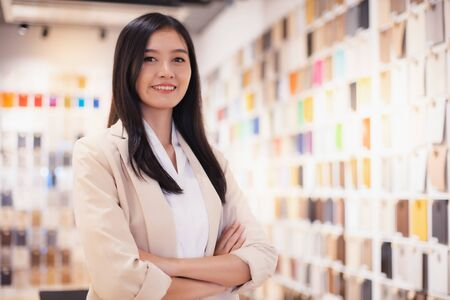 Smiling Asian business woman  looking   tablet  stay material room .young Asian business executive happy.
