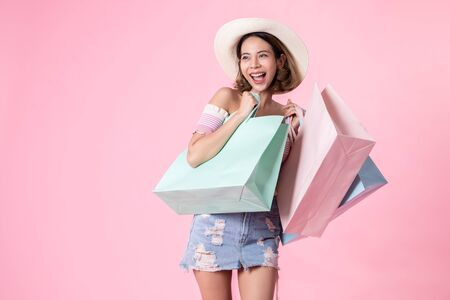 Asian pretty young woman walking over pink pastel background. She smiling and holding shopping bags. she nice-looking lovely attractive shine She holding mobile.