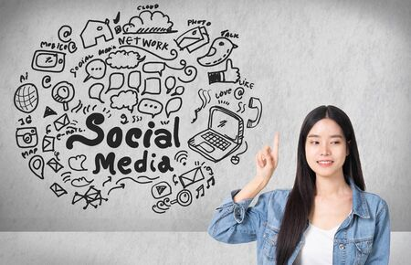Asian young woman looking up of Hand drawn illustration of social media sign and symbol doodles icon.Concrete wall with a social media sketch