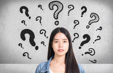 Points d'interrogation avec une jeune femme dans une pose réfléchie. Femme asiatique avec une expression de questionnement et des points d'interrogation au-dessus de sa tête. Icône de question de croquis de dessin à la main.