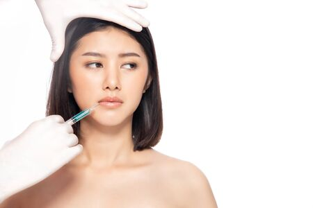 Asain young woman gets injection of botox in her lips. Woman in beauty salon. plastic surgery clinic.Beautiful woman gets botox injection in her face. Stock fotó