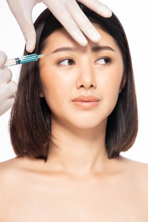 Asian young woman gets injection in her lips. Woman in beauty salon. plastic surgery clinic. Beautiful woman gets injection in her face. Stock fotó