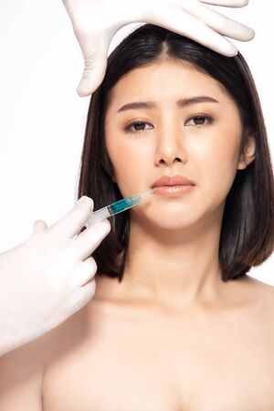 Asian young woman gets injection in her lips. Woman in beauty salon. plastic surgery clinic.Beautiful woman gets injection in her face. Stock fotó