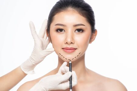 Lines on face, close up, plastic surgery concept, doctors hand in glove making marks on patients face. Asian beauty Woman in beauty salon. plastic surgery clinic.