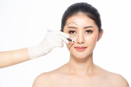 Lines on face, close up, plastic surgery concept, doctors hand in glove making marks on patients face. Asian beauty  Woman in beauty salon. plastic surgery clinic. Stock fotó