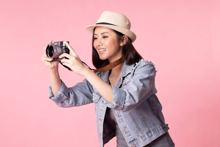 Tourist woman in summer casual clothes. Asian Smiling woman. Passenger traveling abroad to travel on pink background. She going to summer vacation. Travel trip funny.