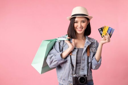 Tourist woman in summer casual clothes. Asian Smiling woman. Passenger traveling abroad to travel on pink background. She going to summer vacation. Travel trip funny Credit card on holiday. Stock fotó