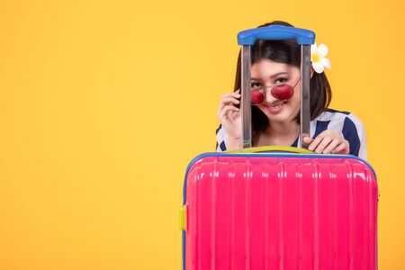 Tourist woman in summer casual clothes.Asian Smiling woman .Passenger traveling abroad to travel on yellow background.Asian woman going to summer vacation.Travel trip funny.