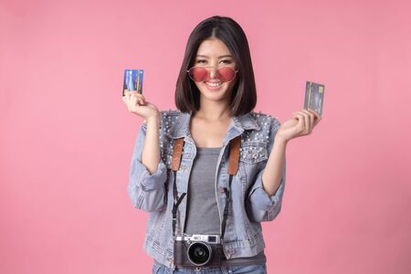 Tourist woman in summer casual clothes.Asian Smiling woman .Passenger traveling abroad to travel on pink background.She going to summer vacation.Travel trip funny Credit card on holiday. Stock fotó