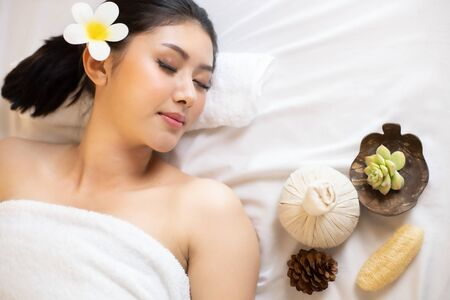 Asian Beautiful, young and healthy woman in spa salon. Massage treatment spa room  . Traditional medicine and healing concept. Banco de Imagens