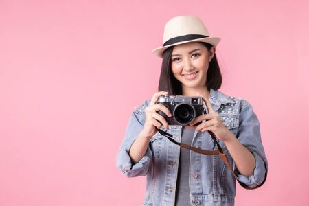 Tourist woman in summer casual clothes.Asian Smiling woman .Passenger traveling abroad to travel on pink background.She going to summer vacation.Travel trip funny with camera. Stock fotó