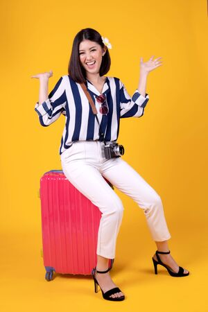Tourist woman in summer casual clothes.Asian Smiling woman .Passenger traveling abroad to travel on yellow background.Asian woman going to summer vacation.Travel trip funny. Stock Photo - 130804268