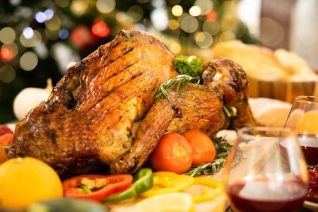 Roasted  chicken or turkey with sauce and grilled autumn vegetables, corn, pumpkin  on wooden table, top view, frame. Christmas or Thanksgiving Day food concept. Stock fotó