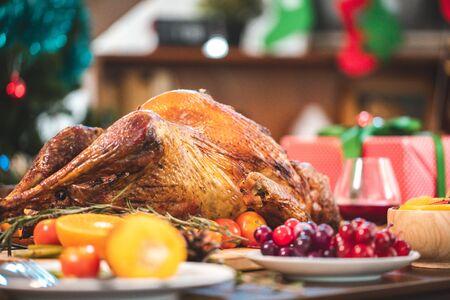 Gebratenes Huhn oder Truthahn mit Soße und gegrilltem Herbstgemüse: Mais, Kürbis auf Holztisch, Draufsicht, Rahmen. Weihnachts- oder Thanksgiving-Food-Konzept. Standard-Bild