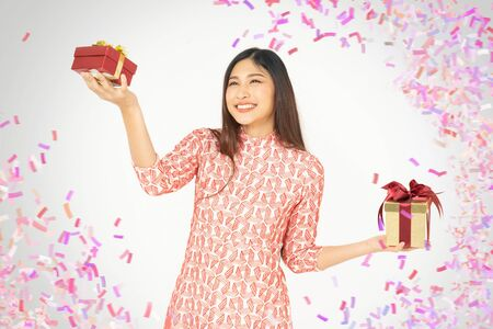 Photo of asian curious woman in red dress rejoicing her birthday or new year gift box. Young woman holding gift  box with red bow being excited and surprised  holiday present isolated white background 免版税图像 - 133204636