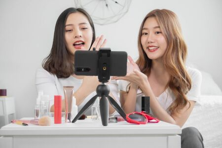 Portrait of young asian woman review giveaway gift product fan following channel, recording video make up lipstic cosmetic at home. Beauty blogger present beauty cosmetics