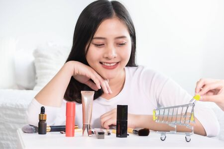 Asian woman shopping online for new dress. All content is made up.Model shopping cart, basket.Online shopping concept Stock Photo