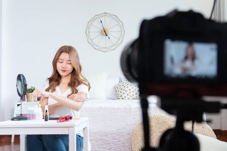 Portrait of young asian woman review giveaway gift product fan following channel, recording video make up lipstic cosmetic at home. Beauty blogger present beauty cosmetics Foto de archivo - 134648593