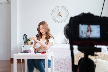 Portrait of young asian woman review giveaway gift product fan following channel, recording video make up lipstic cosmetic at home. Beauty blogger present beauty cosmetics Foto de archivo - 134648607