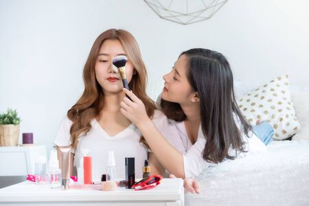 Portrait of young asian woman review giveaway gift product fan following channel, recording video make up lipstic cosmetic at home. Beauty blogger present beauty cosmetics Foto de archivo - 134648713