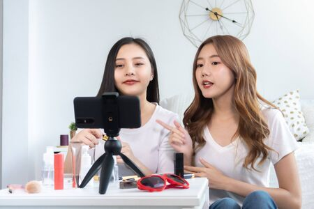 Portrait of young asian woman review giveaway gift product fan following channel, recording video make up lipstic cosmetic at home. Beauty blogger present beauty cosmetics Foto de archivo - 134648992