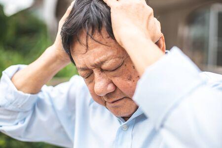 Portrait of an elderly man with headache.senior man covering his face with his hands.vintage tone Foto de archivo - 134712725