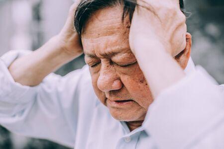 Portrait of an elderly man with headache.senior man covering his face with his hands.vintage tone Foto de archivo - 134712726