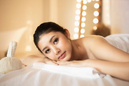 Asian Beautiful, young and healthy woman in spa salon. Massage treatment spa room  . Traditional medicine and healing concept. Stock Photo