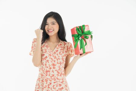 Photo of asian curious woman in red dress rejoicing her birthday or new year gift box. Young woman holding gift  box with red bow being excited and surprised  holiday present isolated white  background Foto de archivo - 134712787