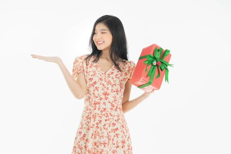 Photo of asian curious woman in red dress rejoicing her birthday or new year gift box. Young woman holding gift  box with red bow being excited and surprised  holiday present isolated white  background Foto de archivo - 134712788
