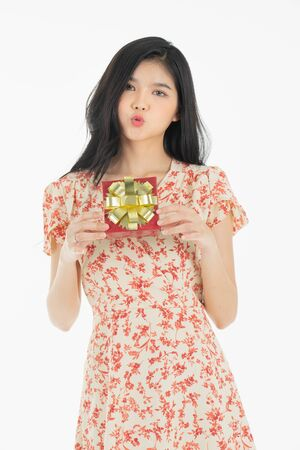 Photo of asian curious woman in red dress rejoicing her birthday or new year gift box. Young woman holding gift  box with red bow being excited and surprised  holiday present isolated white  background 免版税图像 - 134712791