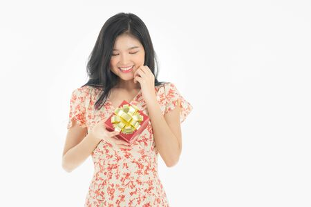 Photo of asian curious woman in red dress rejoicing her birthday or new year gift box. Young woman holding gift  box with red bow being excited and surprised  holiday present isolated white  background Foto de archivo - 134930615