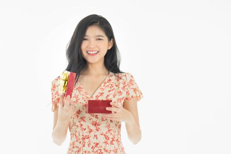 Photo of asian curious woman in red dress rejoicing her birthday or new year gift box. Young woman holding gift  box with red bow being excited and surprised  holiday present isolated white  background Foto de archivo - 134712794
