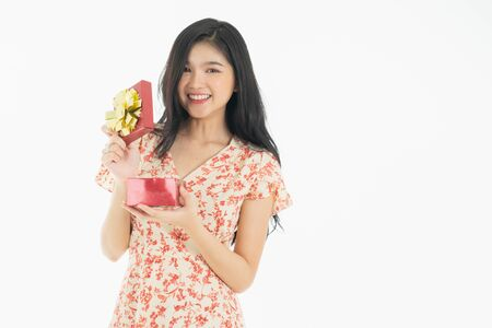 Photo of asian curious woman in red dress rejoicing her birthday or new year gift box. Young woman holding gift  box with red bow being excited and surprised  holiday present isolated white  background Foto de archivo - 134712796