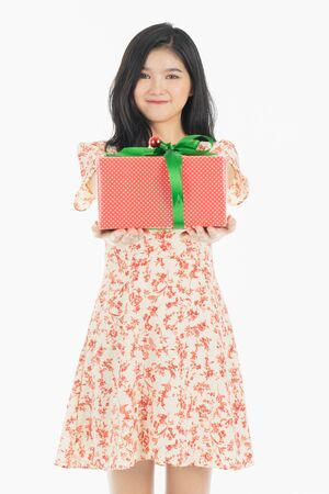 Photo of asian curious woman in red dress rejoicing her birthday or new year gift box. Young woman holding gift  box with red bow being excited and surprised  holiday present isolated white  background Foto de archivo - 134712799