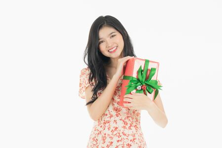 Photo of asian curious woman in red dress rejoicing her birthday or new year gift box. Young woman holding gift  box with red bow being excited and surprised  holiday present isolated white  background Foto de archivo - 134712803