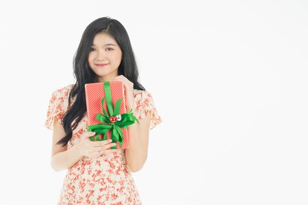 Photo of asian curious woman in red dress rejoicing her birthday or new year gift box. Young woman holding gift  box with red bow being excited and surprised  holiday present isolated white  background Foto de archivo - 134712817