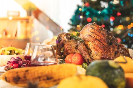 Roasted  chicken or turkey with sauce and grilled autumn vegetables: corn,pumpkin  on wooden table, top view, frame. Christmas or Thanksgiving Day food concept. Foto de archivo - 135133539