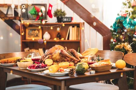 Roasted  chicken or turkey with sauce and grilled autumn vegetables: corn, pumpkin  on wooden table, top view, frame. Christmas or Thanksgiving Day food concept. Foto de archivo - 134656840
