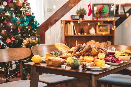 Gebratenes Huhn oder Truthahn mit Soße und gegrilltem Herbstgemüse: Mais, Kürbis auf Holztisch, Draufsicht, Rahmen. Weihnachts- oder Thanksgiving-Food-Konzept.