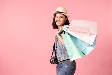 Tourist woman in summer casual clothes.Asian Smiling woman .Passenger traveling abroad to travel on pink background.She going to summer vacation.Travel trip funny Credit card on holiday. Foto de archivo - 135607786
