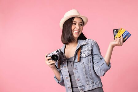 Tourist woman in summer casual clothes.Asian Smiling woman .Passenger traveling abroad to travel on pink background.She going to summer vacation.Travel trip funny Credit card on holiday. Foto de archivo - 135626472
