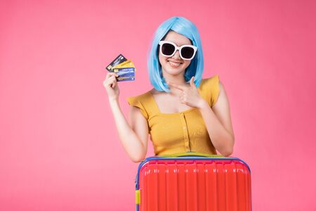 Portrait of a pretty excited asian girl with colorful baggage on  isolated over pink background .Asian travel  woman carrying in colorful for summer trip concept .young blue hair girl . Foto de archivo - 135518613
