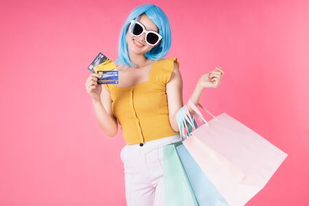 Portrait of a pretty excited asian girl with colorful shopping bags showing  isolated over pink background .Asian shopaholic woman carrying shopping bags in colorful for summer sale concept .young blue hair girl . Foto de archivo - 135626494