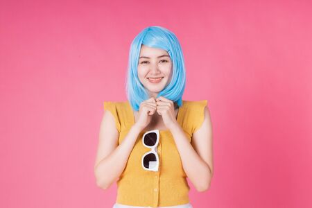 Portrait of a pretty excited asian girl with colorful shopping bags showing  isolated over pink background .Asian shopaholic woman in colorful for summer sale concept .young blue hair girl . Foto de archivo - 135626493
