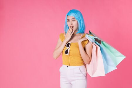 Portrait of a pretty excited asian girl with colorful shopping bags showing  isolated over pink background .Asian shopaholic woman carrying shopping bags in colorful for summer sale concept .young blue hair girl . Foto de archivo - 135626513