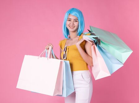 Portrait of a pretty excited asian girl with colorful shopping bags showing  isolated over pink background Asian shopaholic woman carrying shopping bags in colorful for summer sale concept young blue hair girl Foto de archivo - 135627805
