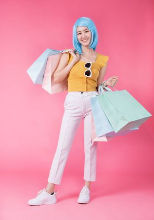 Portrait of a pretty excited asian girl with colorful shopping bags showing  isolated over pink background Asian shopaholic woman carrying shopping bags in colorful for summer sale concept young blue hair girl Foto de archivo - 135627853