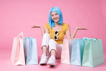 Portrait of a pretty excited asian girl with colorful shopping bags showing  isolated over pink background .Asian shopaholic woman carrying shopping bags in colorful for summer sale concept young blue hair girl Foto de archivo - 135627902
