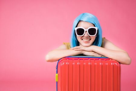 Portrait of a pretty excited asian girl with colorful baggage on  isolated over pink background Asian travel  woman carrying in colorful for summer trip concept young blue hair girl Foto de archivo - 135628110
